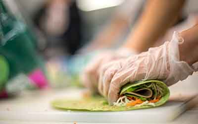 Hands rolling up a healthy turkey wrap